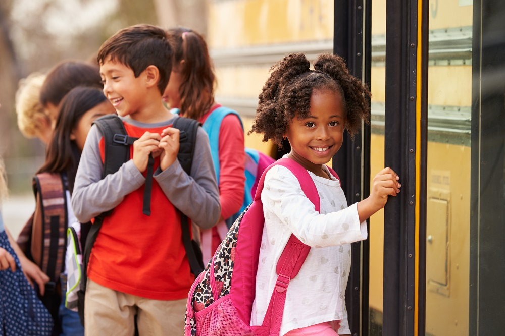 Child with backpack and school bus